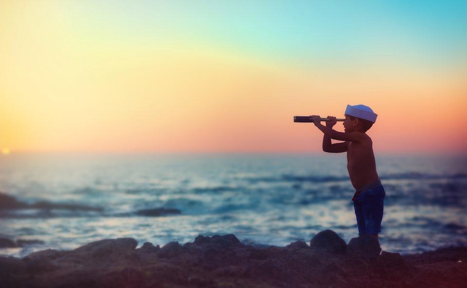 Мальчик смотрит в подзорную трубу что бы увидеть смысл жизни